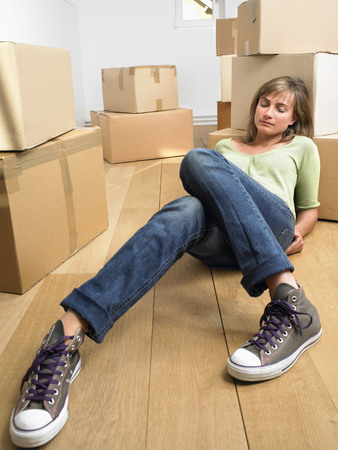 attics: Woman sleeping on floor with moving boxes around her. LANG_EVOIMAGES