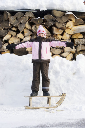 abodes: Young girl standing on sledge LANG_EVOIMAGES