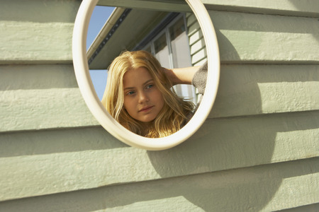 selfish: Young Woman Looking in Mirror outside. LANG_EVOIMAGES