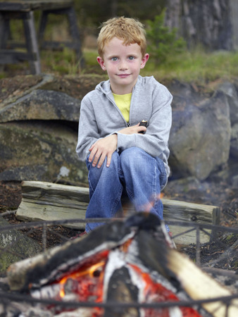 ablaze: Young boy sitting by fire pit holding a hot dog.