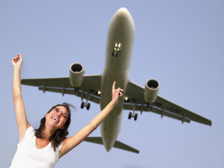 offset up: Woman smiling with arms outstretched standing below a plane flying overhead. LANG_EVOIMAGES