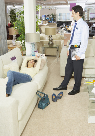 down lights: Woman lying on sofa in furniture store.