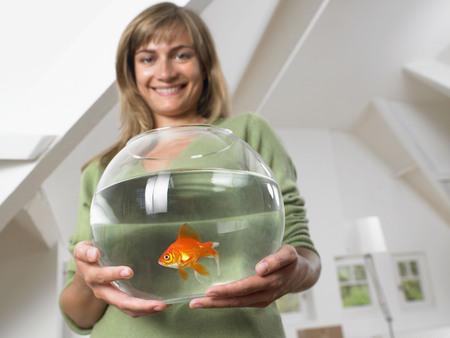Woman holding fishbowl in new home smiling.