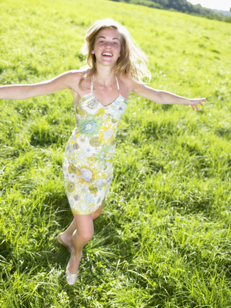 Young woman dancing in a green field. LANG_EVOIMAGES