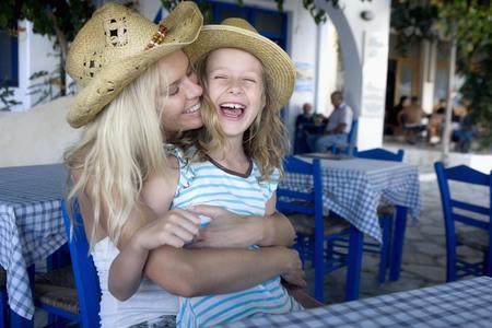 Žena s mladou dívkou ve venkovní restauraci s úsměvem. LANG_EVOIMAGES