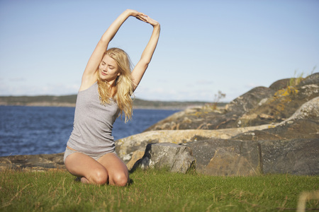Young Woman doing Yoga on grass by sea.