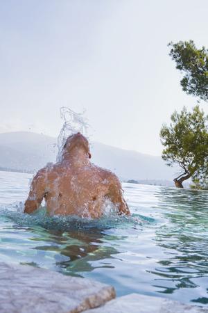 rejuvenated: Young man splashing in a pool