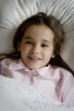 Portrait of a young girl in bed.
