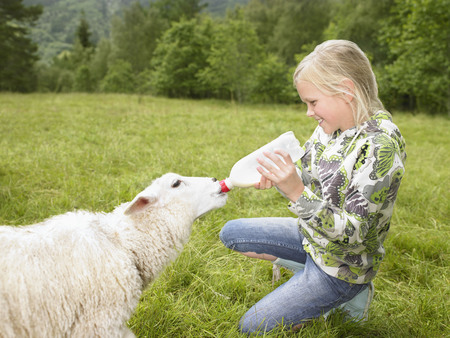 Young girl smiling and feeding a lamb with a bottle in a field.