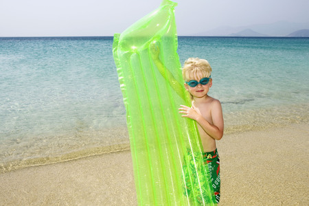 Young boy at the beach with an inflatable raft.