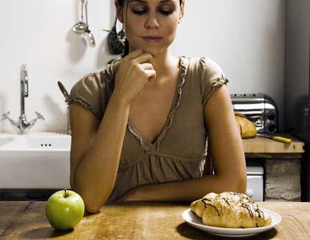 willpower: Woman at table with apple and pastry.