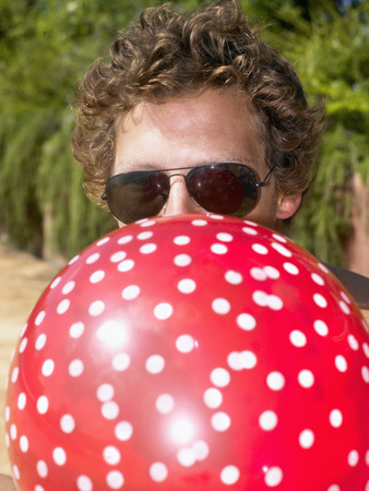 Man blowing up a balloon and wearing sunglasses.