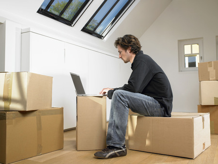 attics: Man sitting with laptop on moving box. LANG_EVOIMAGES