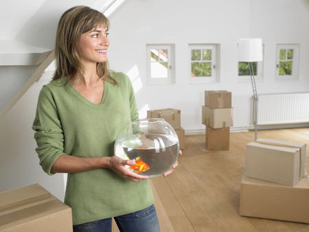 cardboard only: Woman holding fishbowl in new home smiling.