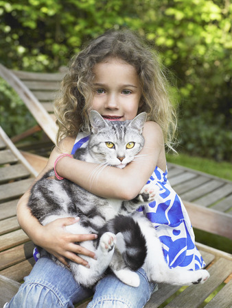Young girl outdoors smiling with a cat on her lap.