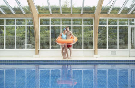 windowpanes: Couple standing in rubber ring by pool. LANG_EVOIMAGES