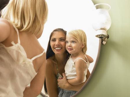 grooming: Mother and daughter looking at mirror.