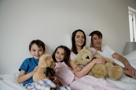 tot: Portrait of a family sitting on a bed. LANG_EVOIMAGES