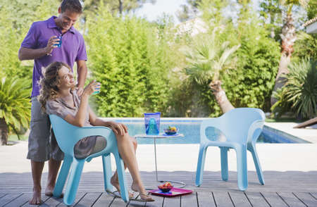 personas abrazadas: Couple on a wooden terrace by a pool
