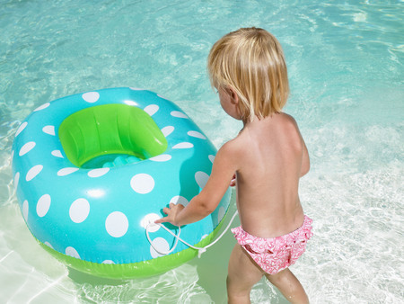 Young boy playing with an inner tube in a pool.