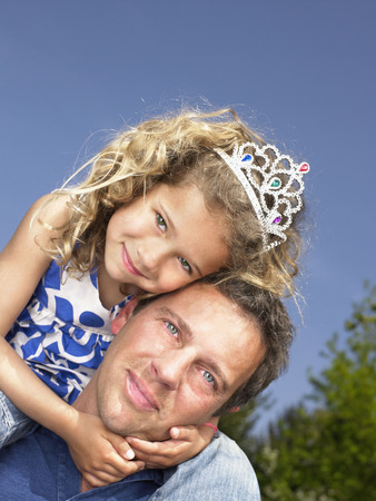 Man with smiling young girl wearing tiara on shoulders.