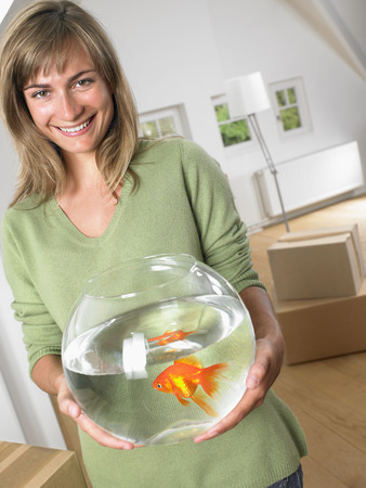 attics: Woman holding fishbowl in new home smiling.