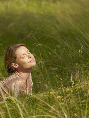 sweden resting: Woman lying in the grass with eyes closed smiling. LANG_EVOIMAGES