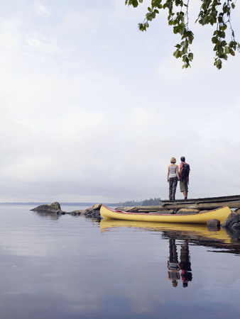 ruck sack: Couple holding hands on a dock near a boat.