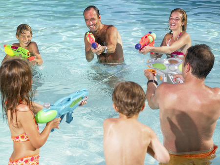 Kids and adults playing with water guns.