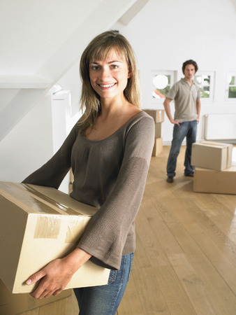 cardboard only: Couple moving into new home smiling. LANG_EVOIMAGES