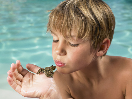 Boy holding a frog in his hand.