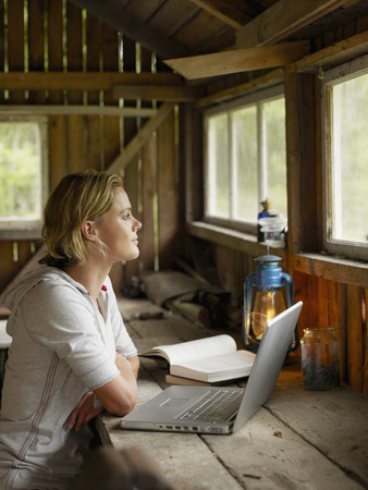 information age: Woman with laptop and book sitting at table in cabin. LANG_EVOIMAGES