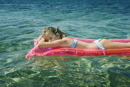 Young girl sleeping floating on an inflatable raft.
