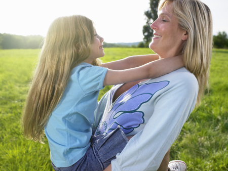 Mother and daughter playing in a field.