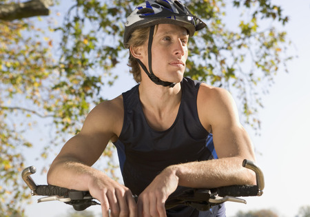 in low spirits: Portrait of cyclist with helmet and bike.