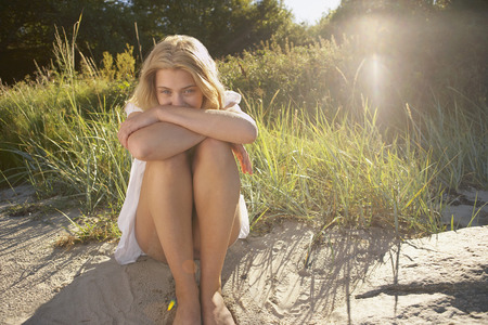 Young Woman Sitting at edge of beach.