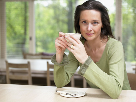 Woman holding a mug at a table indoors smiling.