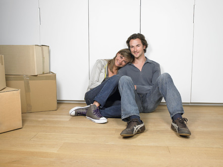 cardboard only: Couple sitting on floor smiling with moving boxes nearby. LANG_EVOIMAGES