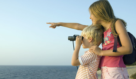 Young girl pointing out over the sea smiling with young boy using binoculars. LANG_EVOIMAGES