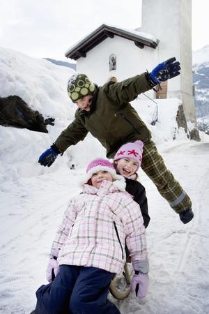 Children sledging down slope LANG_EVOIMAGES