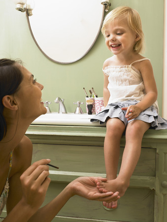 full length mirror: Mother and daughter applying makeup.