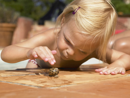 Little girl playing with a snail.
