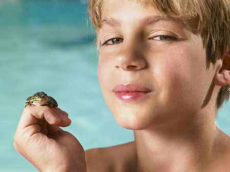 tweens: Boy holding a frog in his hand.