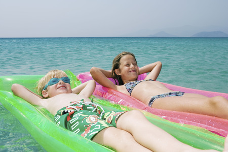 two persons only: Young boy and young girl floating on inflatable rafts in the water smiling.