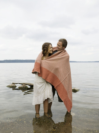 gals: Man and woman standing in shallow water LANG_EVOIMAGES