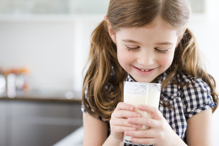 Girl looking into a glass of milk LANG_EVOIMAGES