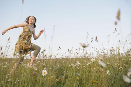 Girl runs through field, looks at sun LANG_EVOIMAGES