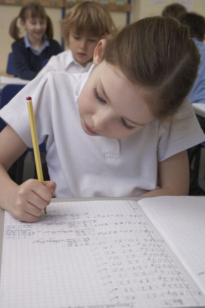 formulae: Girl writing in classroom LANG_EVOIMAGES