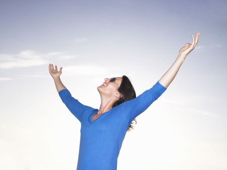 Woman stretching her arms, blue sky LANG_EVOIMAGES