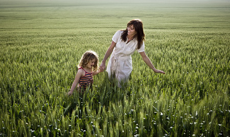 Woman and child walking in wheat-field LANG_EVOIMAGES